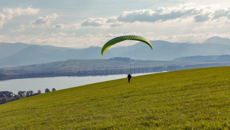 Gleitschirm beginnt Flug vom Hügel Extrem trägt Tätigkeit zur Schau stockfoto