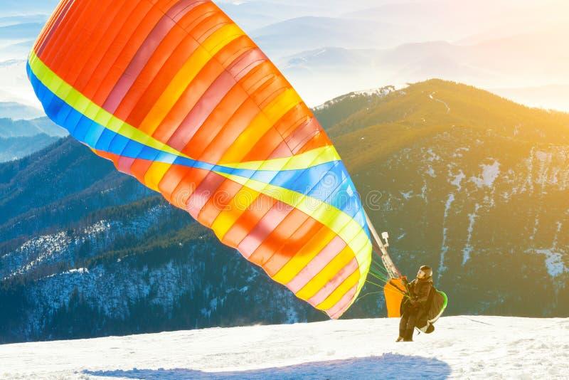 Gleitschirm, der in Luft von der Spitze eines schneebedeckten Berghangs mit Sonne hinter seinen zurück startet stockbild