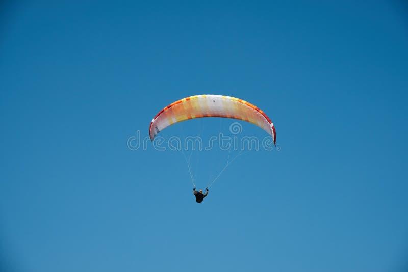 Gleitschirm fliegt in den blauen Himmel Gleitschirmfliegen im Himmel an einem sonnigen Tag lizenzfreies stockbild