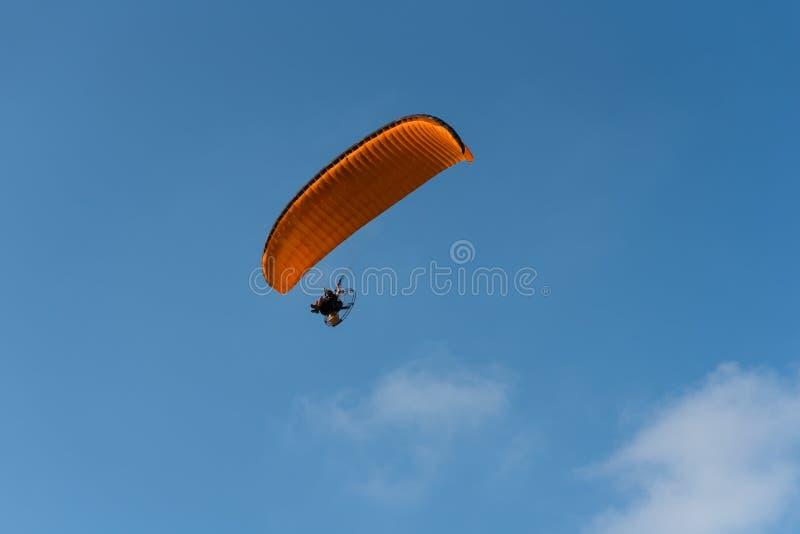 Gleitschirm fliegt orange Gleitschirm im blauen Himmel paragliding lizenzfreies stockfoto