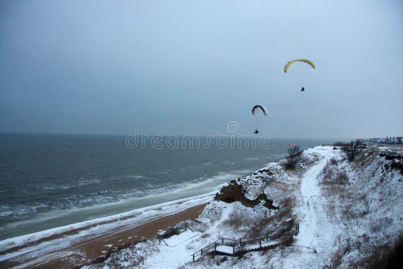 Gleitschirme über dem kalten Meer lizenzfreie stockfotografie