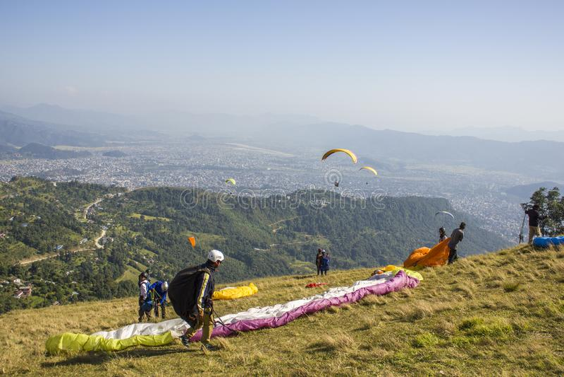 Gleitschirme auf dem Abhang bereiten vor sich, sich gegen den Hintergrund der Stadt in einem grünen Berg zu entfernen lizenzfreies stockbild
