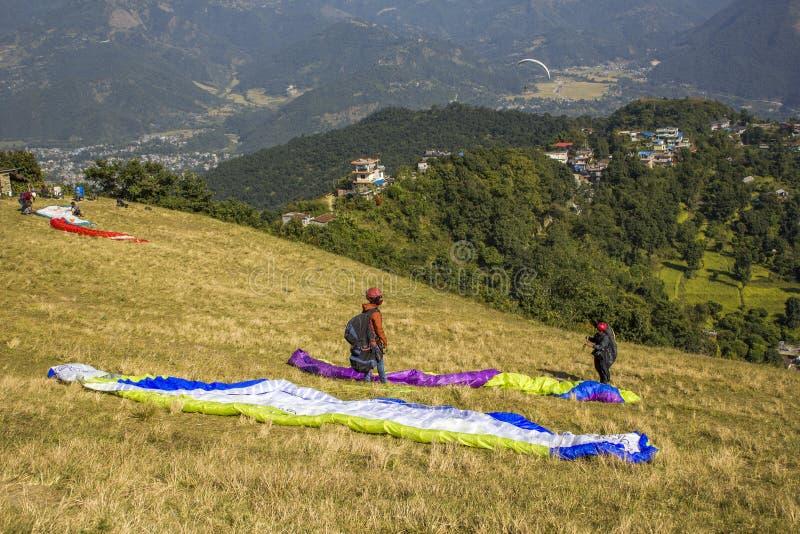 Gleitschirme auf dem Bergabhang bereiten vor sich, sich auf dem Hintergrund von grünen Bergen und von Häusern herein zu entfernen lizenzfreie stockfotografie
