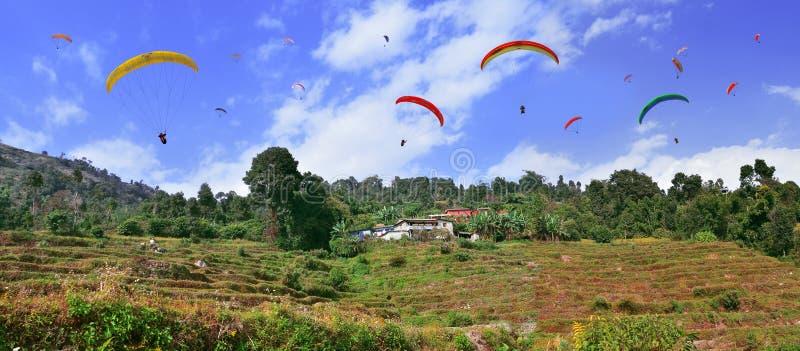 Gleitschirme, die über den Himalaja und die Reisfelder fliegen stockfoto
