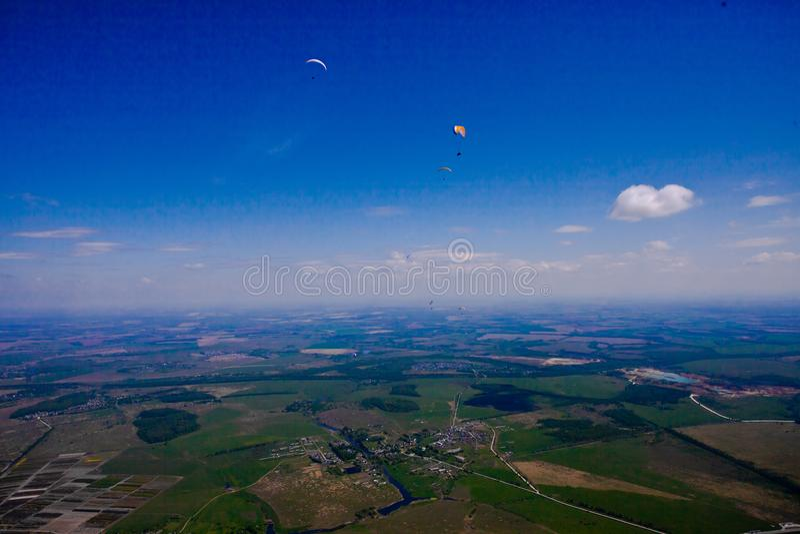 Gleitschirme fliegen über die Grünebene unter den blauen Himmel stockfotos
