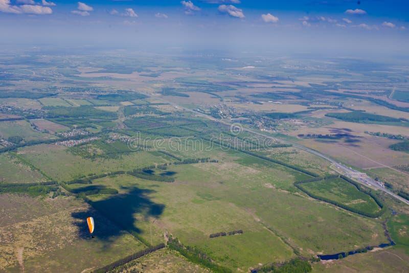 Gleitschirme fliegen über die Grünebene unter den blauen Himmel lizenzfreies stockfoto
