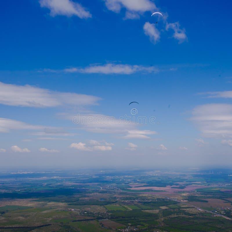 Gleitschirme fliegen über die Grünebene unter den blauen Himmel lizenzfreie stockfotografie