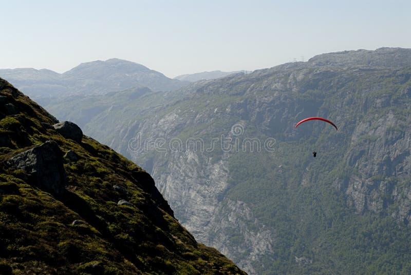 Gleitschirmfliegen über Bergen lizenzfreie stockbilder