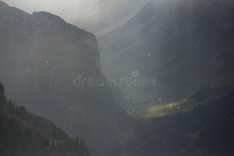 Gleitschirmfliegen über Bergen stockfoto