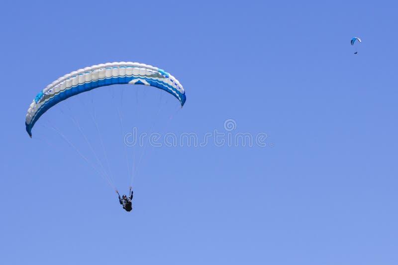 Gleitschirmfliegen im blauen Himmel als Hintergrund lizenzfreie stockfotos