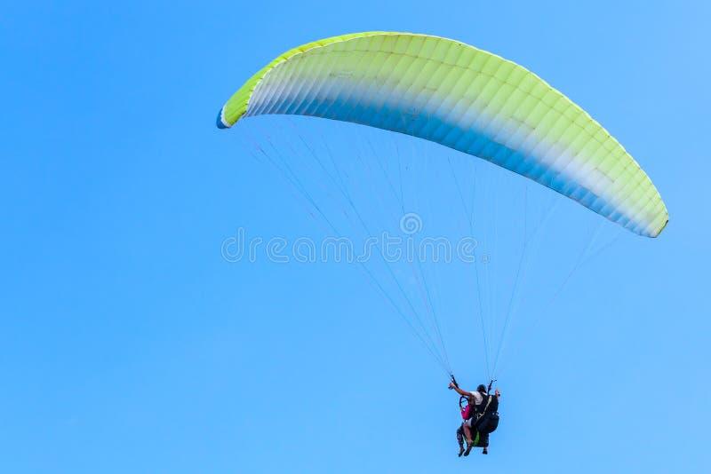 Gleitschirmfliegen im blauen Himmel, im Lehrer und im Anfänger stockfotografie