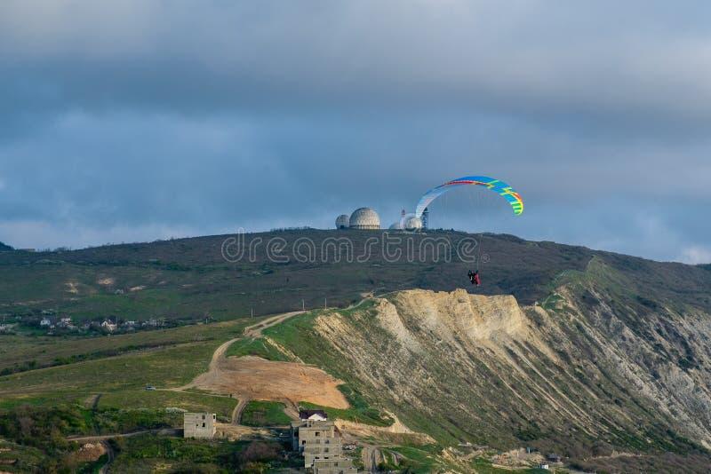 Gleitschirmfliegen im Tandem in den Wolken über den Bergen stockfoto