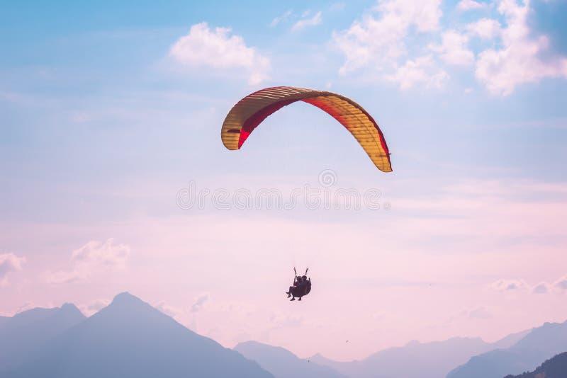 Gleitschirmfliegen im Tandem in Interlaken, die Schweiz Fotografiert im rosa Sonnenunterganglicht Schattenbilder von Gleitschirme lizenzfreie stockfotografie