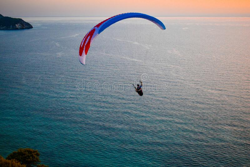 Gleitschirmfliegen während eines Sommersonnenuntergangs auf der Insel von Lefkas in Griechenland lizenzfreie stockfotografie