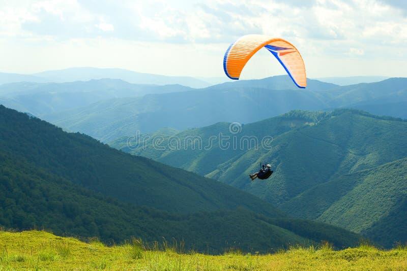 Gleitschirmfliegentief über Spitze von grünen Karpatenbergen stockfotografie