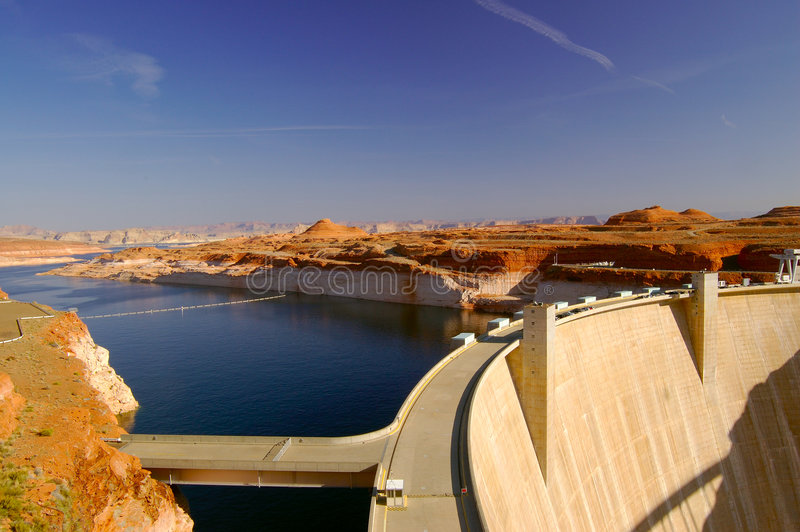 Glen Canyon Dam 2. Glen Canyon Dam in Page, Arizona lit by morning sun with cars parked on the road running along its' top stock photography