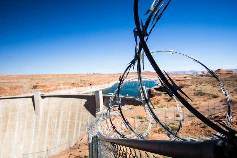 Glen Canyon Dam e lago Powell com a cerca protetora e do impedimento do arame farpado imagem de stock