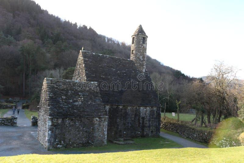 GLENDALOUGH, IRLANDA - 20 de febrero de 2018: El cementerio antiguo en el sitio monástico Glendalough Valle de Glendalough, monta fotografía de archivo