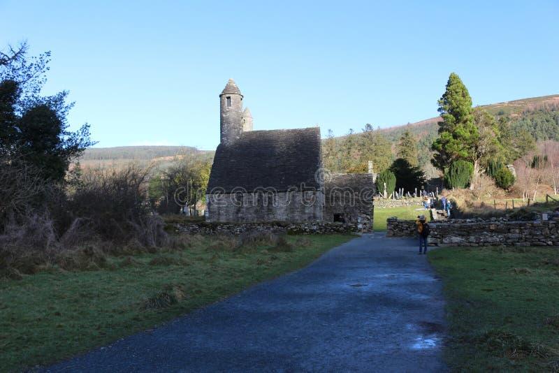 GLENDALOUGH, IRLANDA - 20 de fevereiro de 2018: O cemitério antigo no local monástico Glendalough Vale de Glendalough, montanhas  imagens de stock royalty free