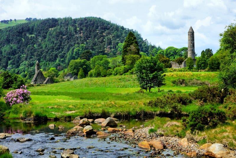 Glendalough kloster- plats med det forntida runda tornet och kyrkan, Wicklow nationalpark, Irland arkivfoto