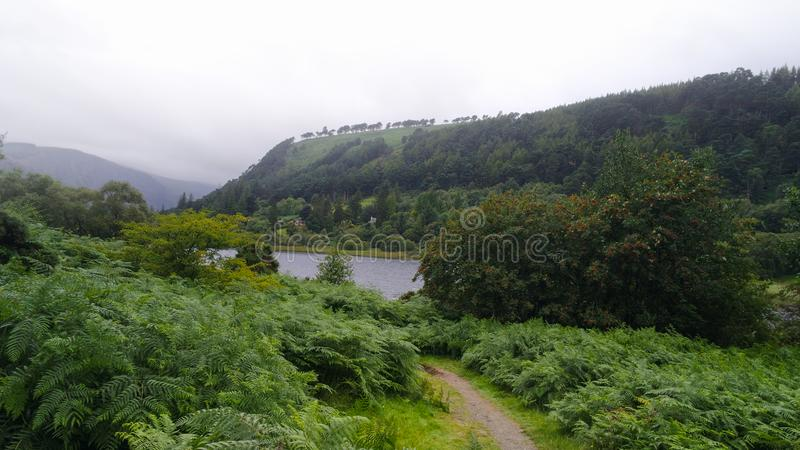 Glendalough and Wicklow Mountains in Ireland with fog on the hills. Glendalough and Wicklow Mountains landscape shot in Ireland with fog on the hills behind lake royalty free stock photo