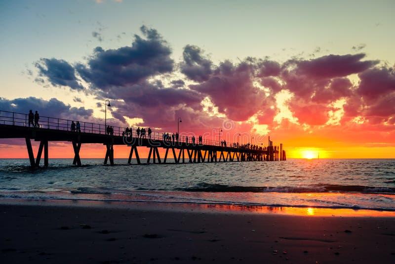 Glenelgpijler met het lopen van mensensilhouetten bij zonsondergang royalty-vrije stock foto's
