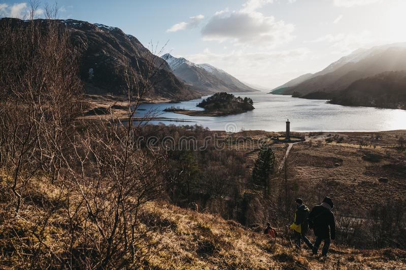People hiking in Glenfinnan, Scotland, Glenfinnan Monument on th royalty free stock photo