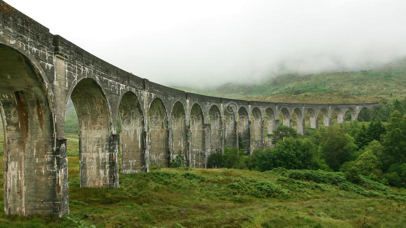 Glenfinnan Viaduct location from Harry Potter movie on overcast day, fog covering hills in background.  stock image