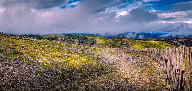 Glenshee山在有木头和铁丝网的苏格兰高地有生苔,石潮湿的地面的在一有薄雾的多云天 免版税图库摄影