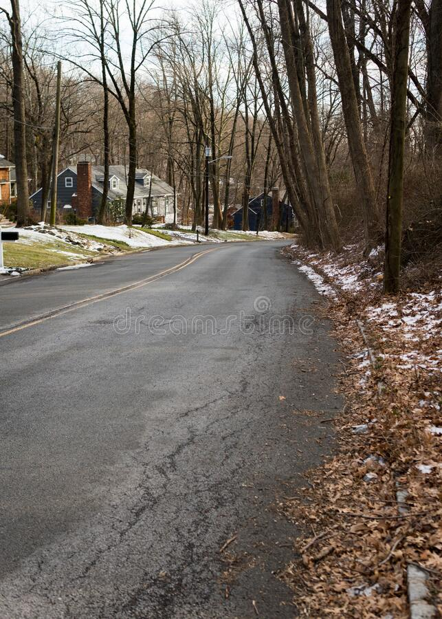 Glenside Ave in Scotch Plains, New Jersey. Old road. Next to Watchung Reservation. Empty street; no people, no traffic. Cloudy day in winter, Trees without stock photography