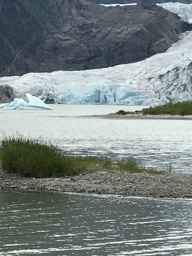 Gletsjer die het water met berg op de achtergrond ontmoeten royalty-vrije stock fotografie