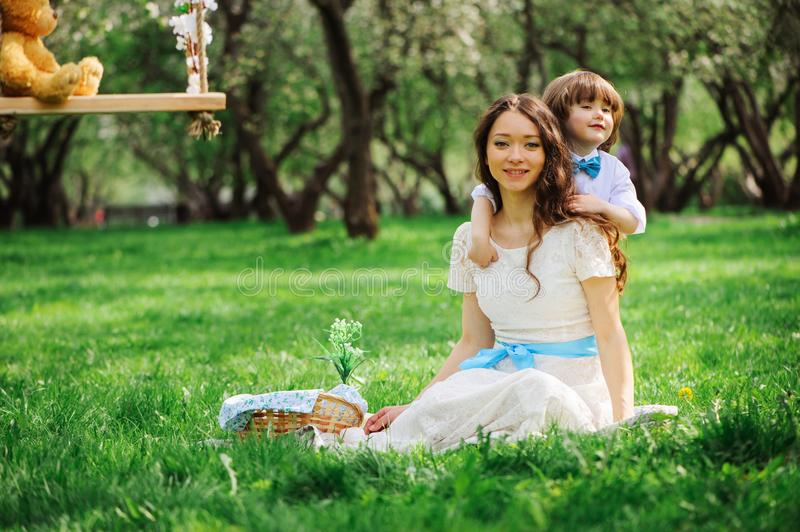 gli abbracci della mamma ed il bambino felici di bacio scherzano il figlio all'aperto in primavera o l'estate fotografia stock libera da diritti