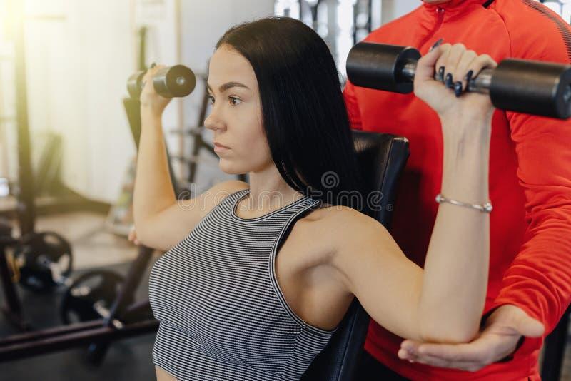 Gli abiti sportivi d'uso della ragazza in una palestra si esercitano della testa di legno, la vettura la aiutano fotografie stock libere da diritti
