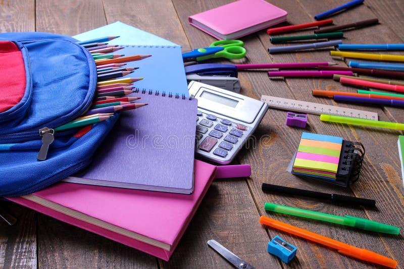 Gli accessori colorati della scuola che cadono da una scuola backpack su una tavola di legno marrone fotografia stock libera da diritti