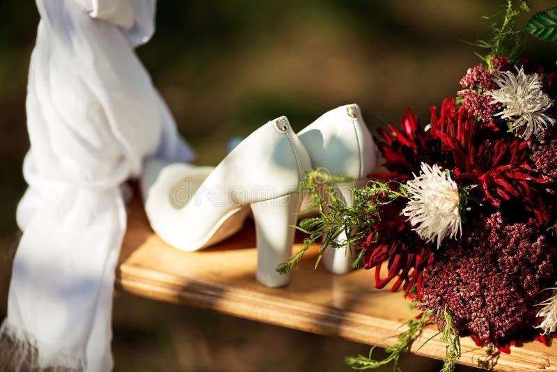 Gli accessori di nozze, bianco hanno tallonato le scarpe per la sposa, mazzo di Borgogna fiorisce su un bordo di legno, mattina d immagine stock