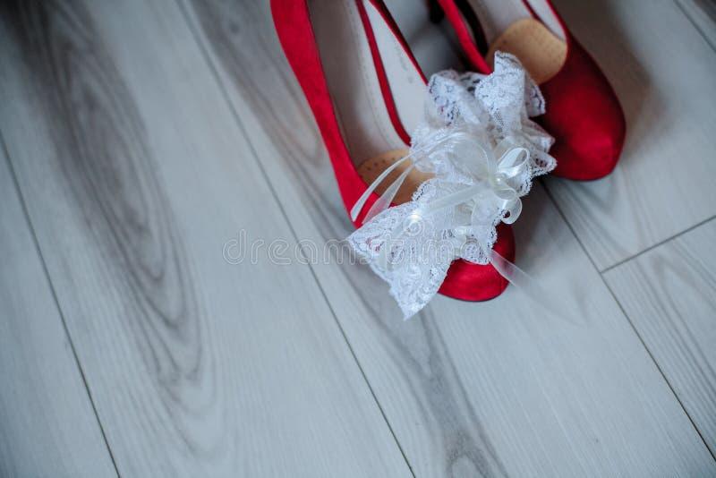 Gli accessori di nozze sotto forma di rosso calza la sposa e la giarrettiera immagine stock