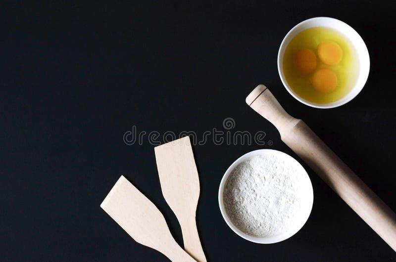 Gli accessori e gli ingredienti della cucina sono posizionati a caso sulla tavola domestica fotografie stock