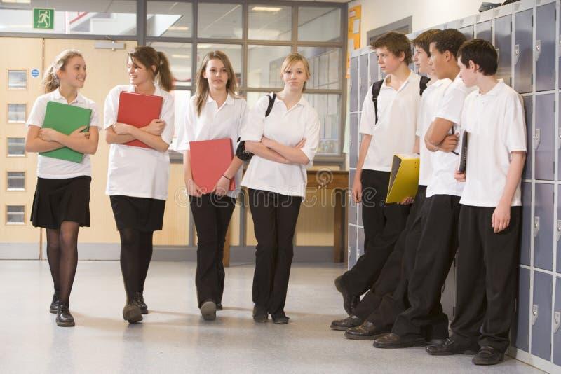 Gli adolescenti che guardano le ragazze camminano giù il corridoio fotografia stock