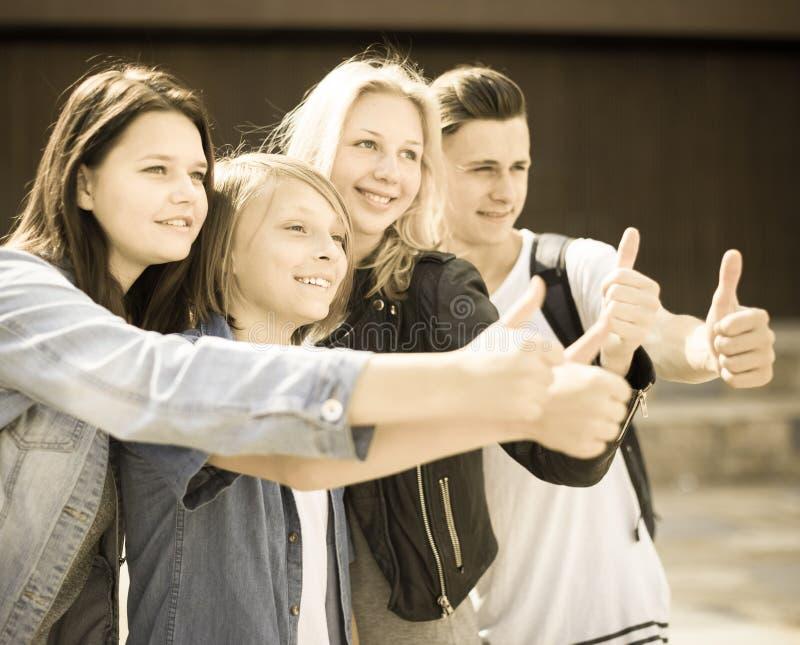Gli adolescenti mostrano i loro pollici su fotografia stock
