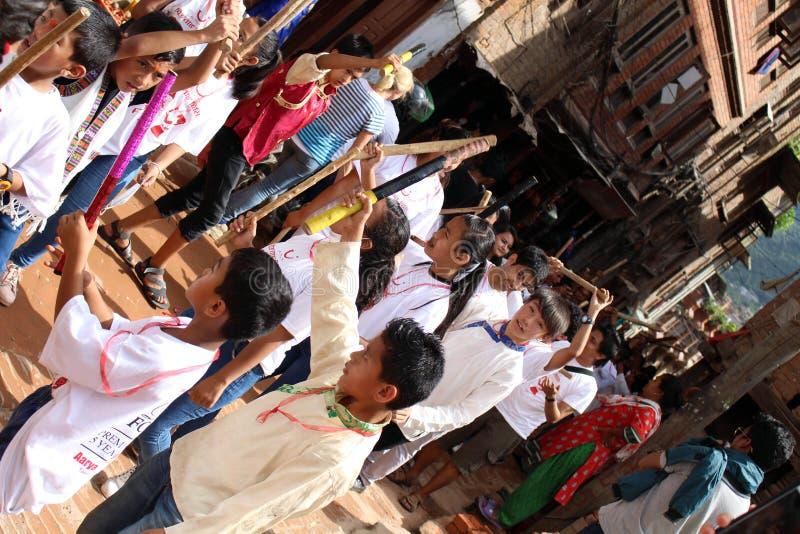 Gli adolescenti nepalesi locali stanno avendo un festival con i bastoni di legno immagine stock libera da diritti