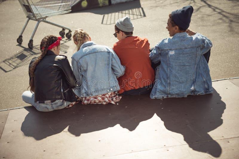 Gli adolescenti raggruppano la seduta insieme e la conversazione a skatepark fotografia stock