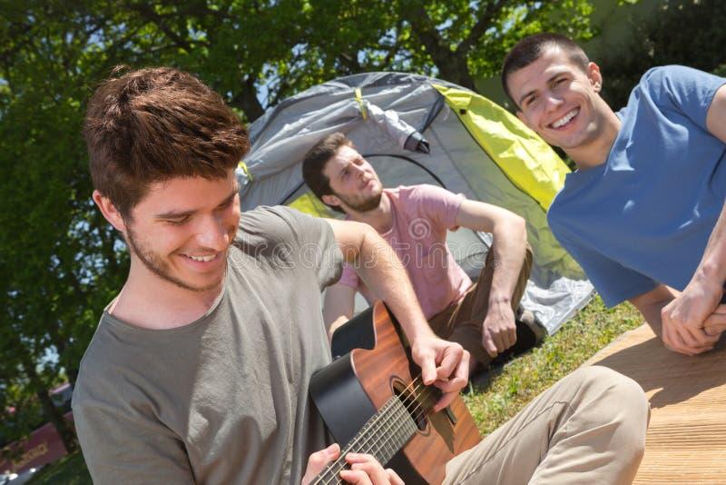 Gli adolescenti si avvicinano alla tenda che gioca la chitarra fotografia stock libera da diritti