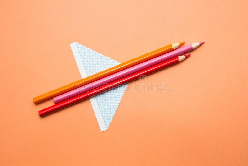 Gli aerei hanno fatto delle matite e della carta su un fondo arancio Di nuovo al banco fotografie stock