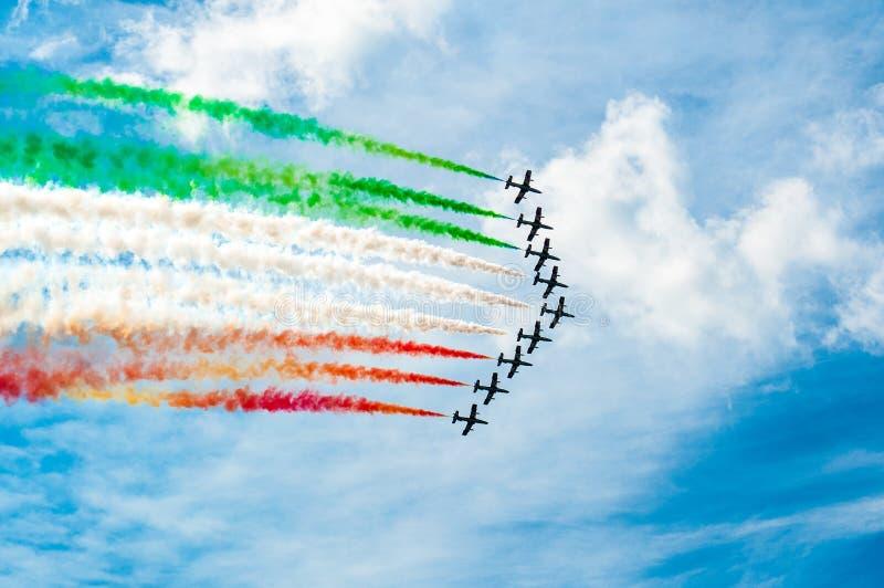 Gli aeroplani acrobatici italiani team la bandiera italiana di disegno in cielo blu fotografia stock libera da diritti