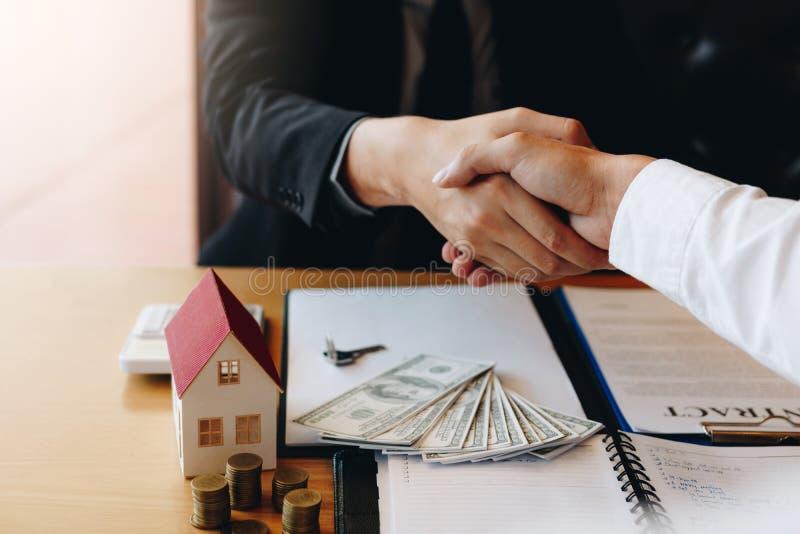 Gli agenti ed i compratori di vendita a domicilio lavorano alla firma delle case nuove ed a stringere le mani fotografia stock libera da diritti