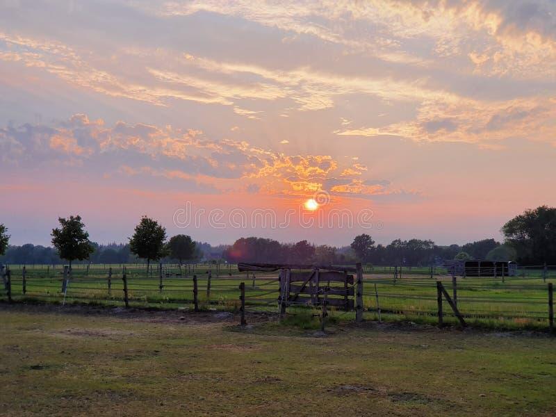 Gli agricoltori sistemano con un tramonto di bellezza immagini stock
