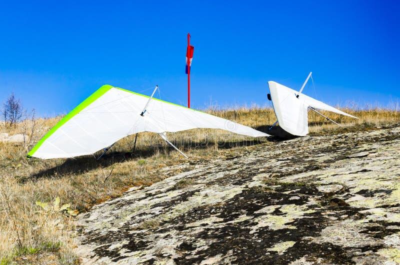 Gli alianti parcheggiati sulla roccia della montagna che aspetta il vento appropriato decollano fotografia stock libera da diritti