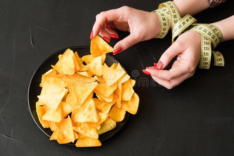 Gli alimenti a rapida preparazione fanno un spuntino la cattiva donna di abitudine di dieta che mangia i chip immagine stock libera da diritti