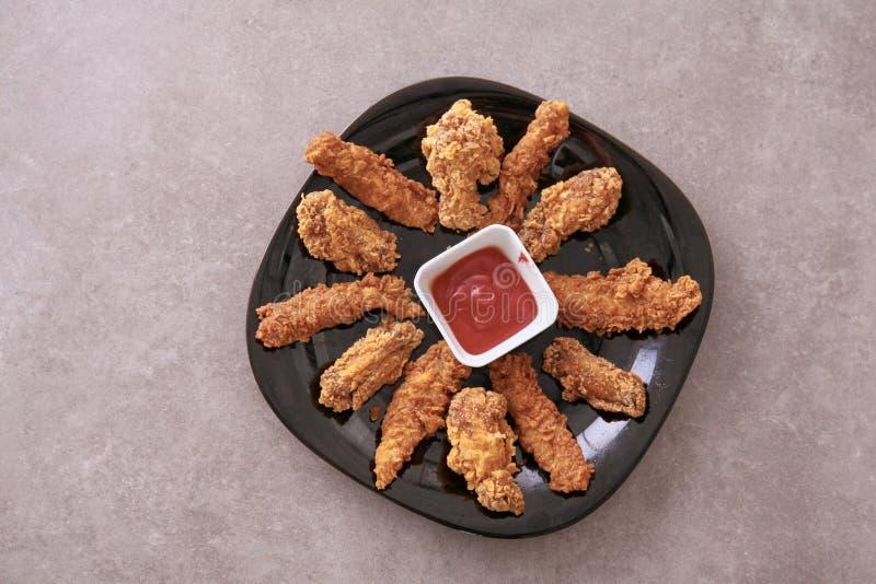 Gli alimenti a rapida preparazione hanno fritto croccante e le patatine fritte piccanti delle coscie di pollo, dell'ala e con sal immagini stock libere da diritti