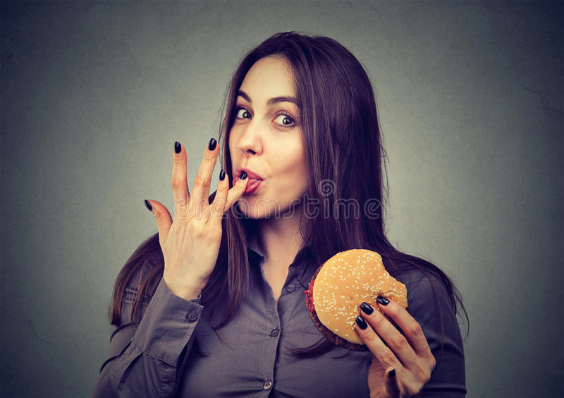 Gli alimenti a rapida preparazione sono il mio favorito Donna che mangia un hamburger che gode del gusto fotografia stock